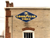 Vintage Goodyear Tires sign on the side of the auto repair shop wall.